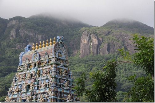 Arulmigu Navasakthi Vinayagar Hindu Temple in Victoria with the granite cliffs of Seychelles in the background
