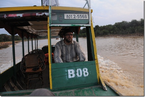 Navigating the channels of Tonlé Sap lake in a longboat.