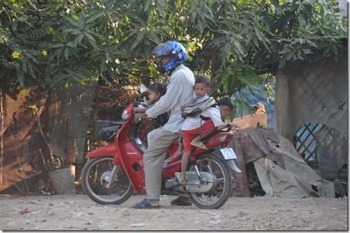Cambodian motorcycle driver taking three kids for a ride in the countryside near Siem Reap, Cambodia