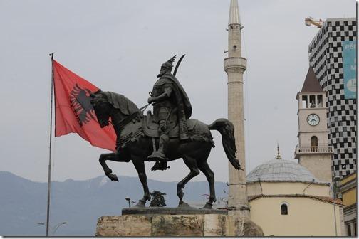 Statue of local Albanian hero George Skanderbeg (Gjergj Kastrioti Skënderbeu) on a horse in Skanderbeg Square (Sheshi Skënderbej) with the Et'hem Bey Mosque (Xhamia e Et'hem Beut) and the Albanian flag in the background