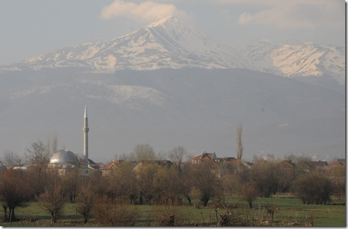 View of the Šar (Sharr) Mountains and a village mosque from a train traveling through the Kosovo countryside.