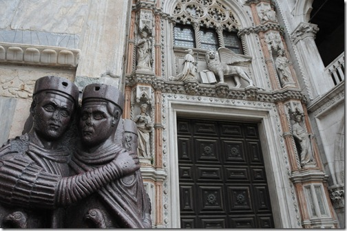 Statue of the Tetrarchs and detail on the front of St. Mark's Basilica, including a Winged Lion of St. Mark in Venice, Italy