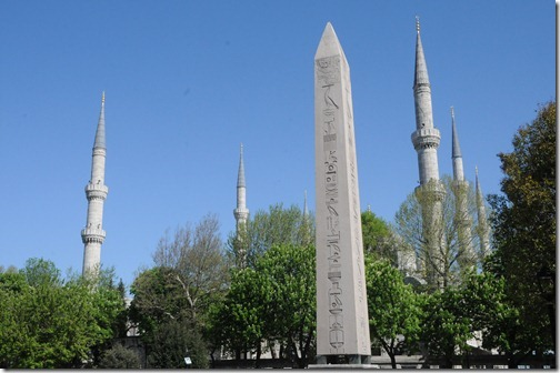 The Obelisk of Thedosius with the minarets of the Sultan Ah in the Ancient Hippodrome of Constantinople (present day Sultan Ahmed (Blue) Mosque in the background in Sultanahmet Mehdani Square in Istanbul, Turkey
