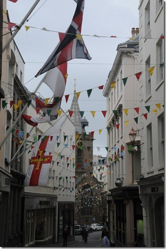 Flags strung across a narrow street in St. Peter Port, Channel Islands (St Pierre Port, Guernesey, Îles d'la Manche)