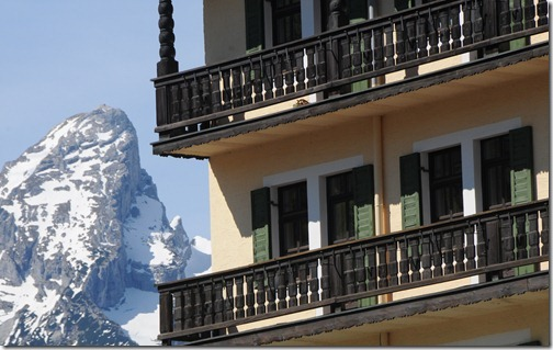 Closeup of the Watzmannfrau peak and a Bavarian building in Berchtesgaden, Germany