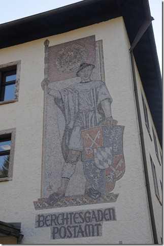 Mural of a Bavarian boy holding a Nazi Flag with the Swastika removed on the Post Office building in Berchtesgaden, Germany