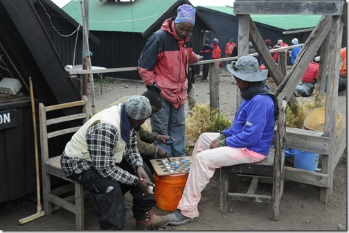 Porters playing a game of checkers with plastic bottle caps at Horombo Camp, Mount Kilimanjaro