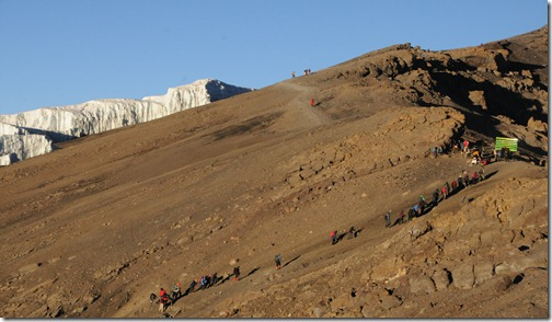 A long chain of hikers climbing up to Stella Point at the rim of the crater of Kibo Peak, Mount Kilimanjaro