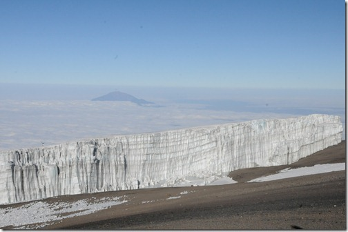 View of the Southern Icefields on Kibo Peak of Mount Kilimanjaro near Uhuru Point with Mount Meru in the distance poking up from the clouds