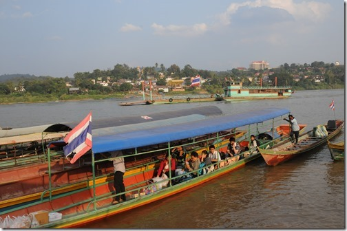 Taking a longboat ferry across the Mekong River into Laos